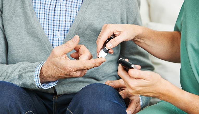 L'infermiera aiuta a misurare il livello di zuccheri nel sangue