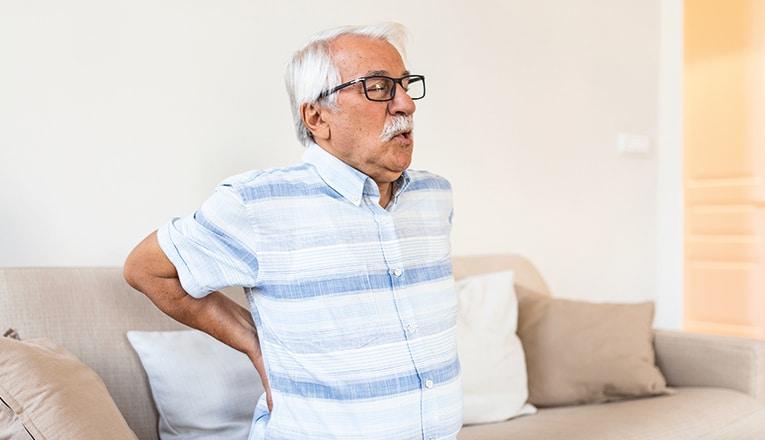 Il signore soffre di dolori alla schiena a causa di un'ernia dorsale