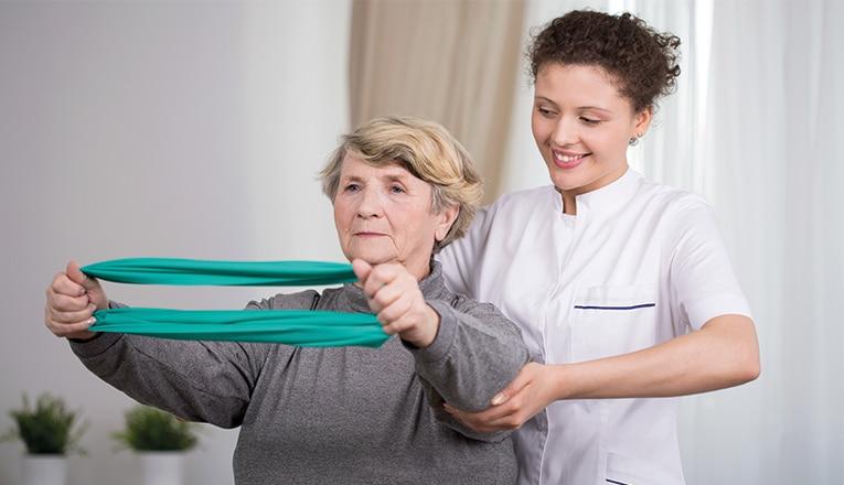 La signora fa esercizi contro un'ernia del disco insieme a un fisioterapista.