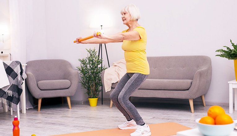 Una donna anziana fa squat come esercizio di fitness.