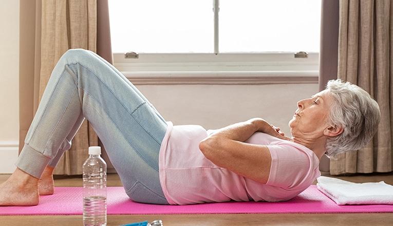 Una donna anziana fa gli addominali come esercizio di fitness.